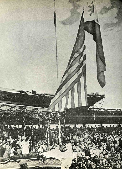 The American flag comes down as the flag of the Phillipines rises in a black and white photo.
